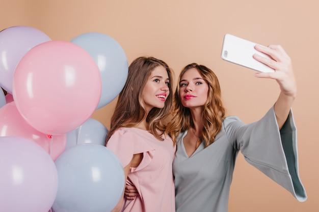 Felice donna con acconciatura ondulata alla moda utilizzando il telefono per selfie con un amico