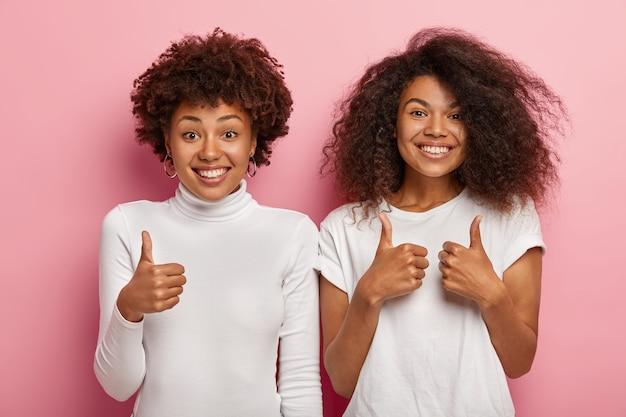 嬉しい女性の親友は親指を立てるサインを作り、元気に笑い、サポートと同意を示します