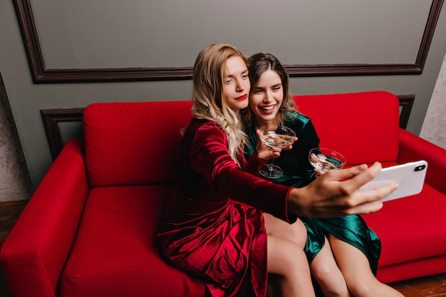 Glad women drinking wine on couch. indoor portrait of winsome girls celebrating something at home.