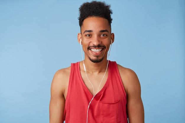 嬉しい若いアフリカ系アメリカ人のハンサムな男は気分が良く、赤いシャツを着て、新しいエキサイティングなポッドキャストを聞いて、広く笑顔