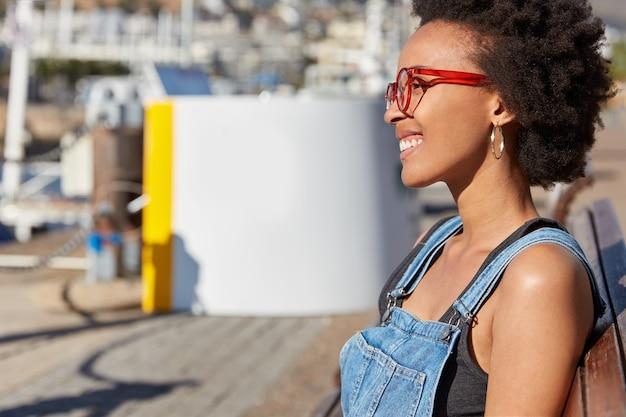 바삭 바삭한 머리카락, 어두운 피부를 가진 기쁜 젊은 미국 소녀는 안경과 캐주얼 옷을 입고 벤치에 앉아 자유 시간을 즐기고 즐거운 것을 꿈꿉니다. 여성 스러움, 스트리트 스타일 및 레저 컨셉