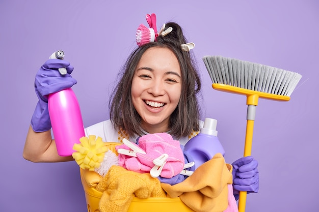 Glad young asian housewife smiles broadly helps about house wears rubber gloves holds cleaning detergent and broom for sweeping floor poses near laundry basket isolated over purple background
