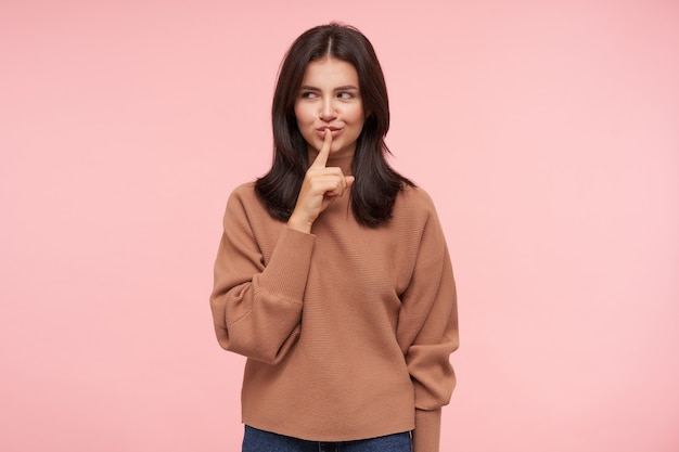 Радостная молодая привлекательная шатенка с распущенными волосами, хитро улыбаясь, поднимая руку с жестом молчания, стоя над розовой стеной в повседневной одежде