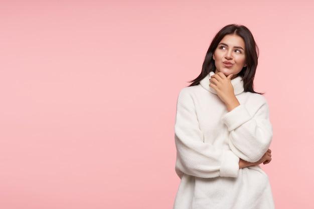 Радостная молодая привлекательная шатенка с естественным макияжем поджимает губы, задумчиво глядя вверх, позирует над розовой стеной в белом полоне