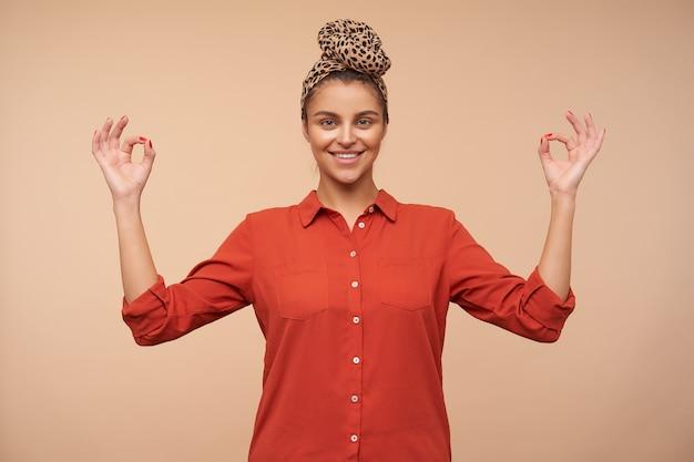 ナマステのサインで手を上げ、ベージュの壁の上に立って、正面で心地よく笑って、自然なメイクでうれしい若い魅力的なブルネットの女性