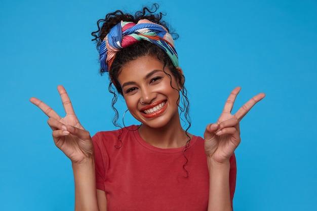 勝利のジェスチャーで手を上げて、青い背景で隔離のカメラで幸せに笑って色のヘッドバンドでうれしい若い魅力的な黒髪の巻き毛の女性