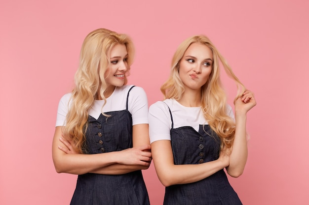 Felice giovane donna attraente con capelli lunghi ondulati guardando allegramente sul suo viso smorfie sorellina perplessa e tirando i capelli con la mano alzata, isolato su sfondo rosa