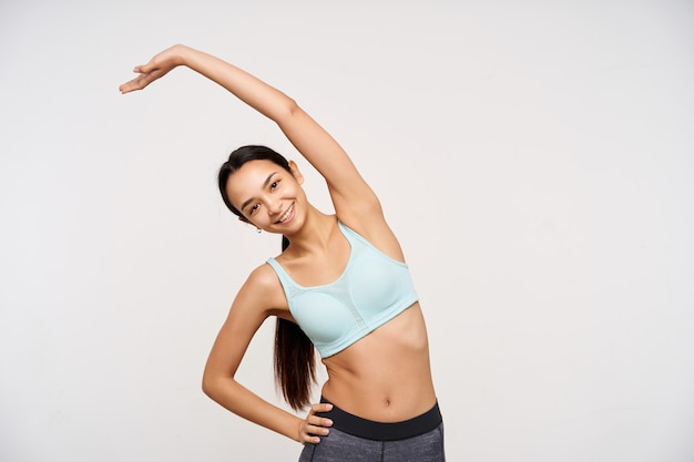 Glad young attractive long haired brunette female with ponytail hairstyle making stretching exercises and smiling happily at front, isolated over white wall
