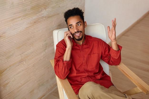 Felice giovane barbuto brunetta dalla pelle scura maschio con taglio di capelli corto tenendo la mano alzata mentre parla al telefono e guardando positivamente da parte, isolato sull'interno della casa