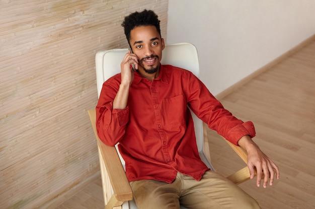 Felice giovane barbuto dalla pelle scura uomo vestito in abbigliamento casual mentre era seduto sulla sedia e effettua chiamate con il suo smartphone, guardando positivamente mentre posa sull'interno di casa
