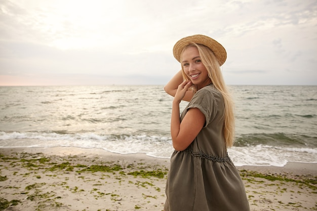 Glad young beautiful long haired blonde lady in boat hat and summer dress smiling cheerfully while looking positively over her shoulder, isolated over beach background