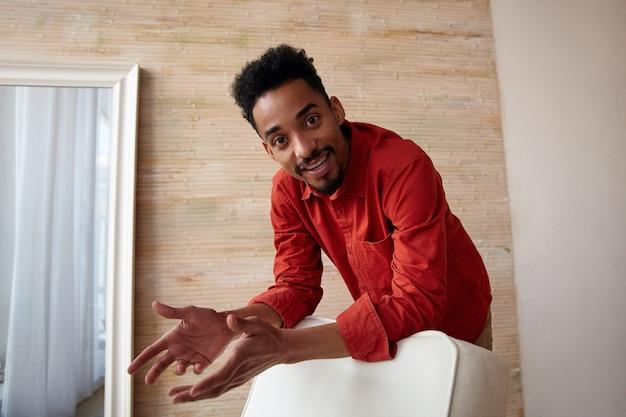 Довольный молодой кареглазый темнокожий брюнет с короткой стрижкой, позитивно выглядящий, опираясь на стул, стоя на домашнем интерьере в красной рубашке