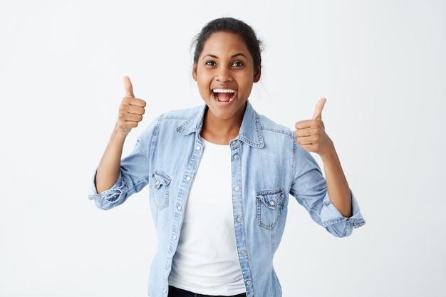 彼女のサポートと誰かへの敬意を示す、親指を立てて元気に笑っているデニム長袖シャツを着てうれしい若い暗い肌の女性。ボディランゲージ。よくやった。