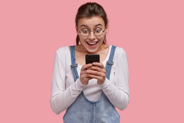 Felice giovane donna europea tiene in mano un moderno telefono cellulare, fissa il fantastico invito alla festa ricevuto via internet, legge impressionanti buone notizie