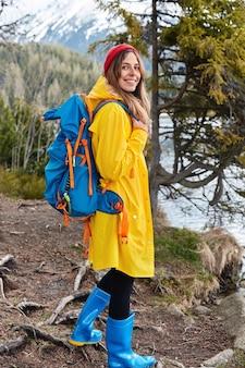 배낭이있는 기쁜 젊은 여성 모델은 빨간 모자, 노란 비옷 및 고무 파란색 부츠를 착용합니다.