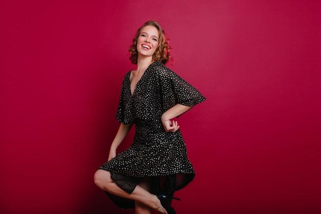 黒の靴で踊る魅力的な笑顔とうれしい若い女性モデル