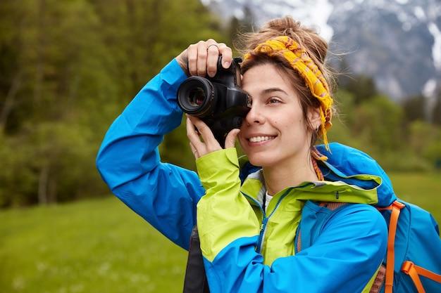 기쁜 젊은 여성 여행자가 전문 카메라로 사진을 촬영하고 그린 필드를 가로 질러 걷는 것을 즐깁니다.