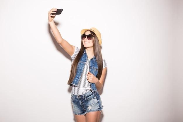Счастливая молодая женщина носит модные оттенки, соломенную шляпу, блузку и шорты, делает селфи на смартфоне, изолированном на белой стене