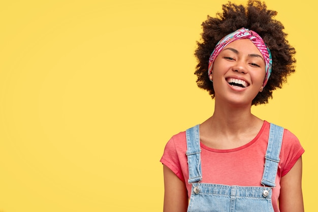 Glad young female with dark skin, white even teeth, laughs positively as sees something funny in front, wears casual t-shirt and dungarees, isolated over yellow wall with blank space aside