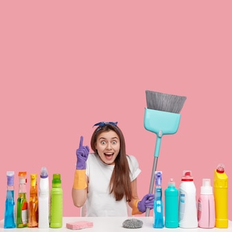 Glad young female with happy expression points above, demonstrates copy space for your advertising content, carries brush or broom