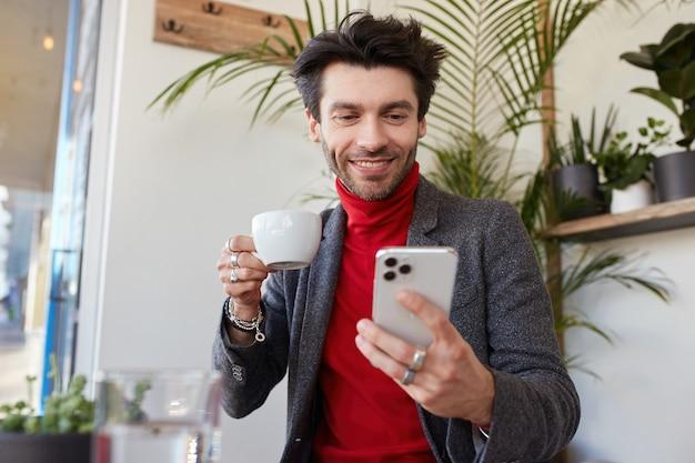 Довольный молодой красивый темноволосый бородатый парень весело смотрит в свой смартфон и держит чашку в поднятой руке, сидя на фоне кафе в официальной одежде