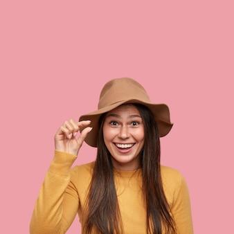 Felice giovane hipster forma un minuscolo oggetto con un dito, sorride volentieri, essendo di buon umore