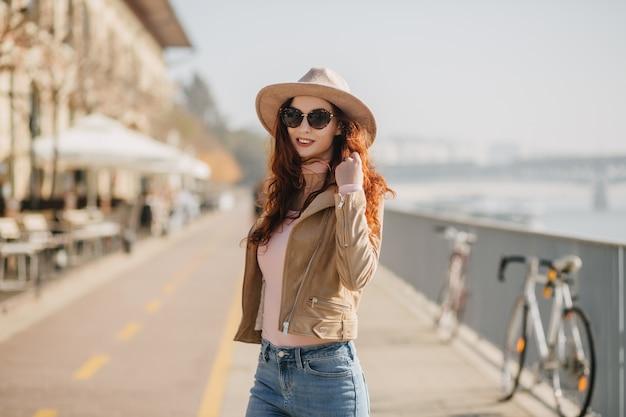 Felice giovane donna indossa giacca e cappello beige che esprimono emozioni positive