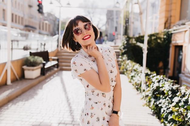 Felice giovane donna in abito bianco sorridente in strada. ragazza bruna dai capelli corti in occhiali da sole che gode della primavera.