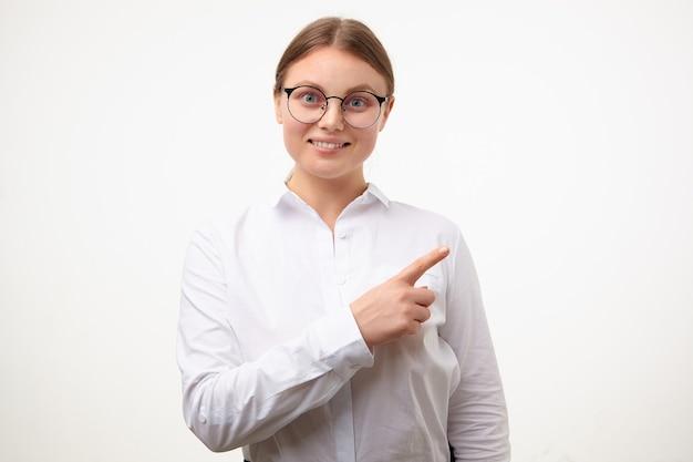 眼鏡をかけた嬉しい若い素敵なブロンドの女性は、人差し指を上げたまま元気に脇を指して、白い背景の上に孤立して広く笑っています