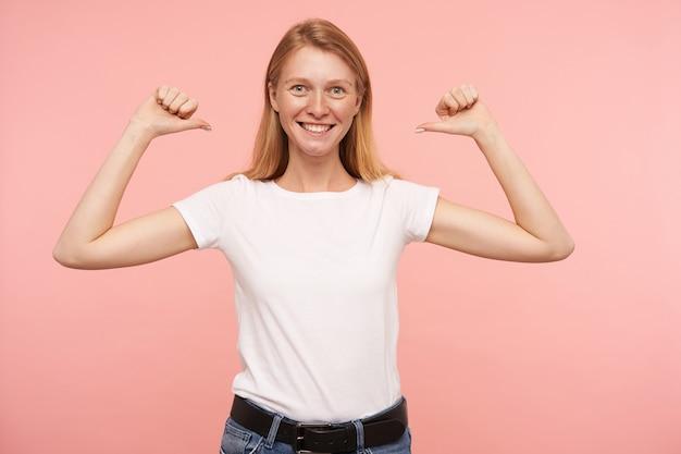カジュアルな髪型で嬉しい若い素敵な女性は、手を上げて幸せに自分自身を指して、元気に笑って、カジュアルな服装でピンクの背景の上にポーズをとる