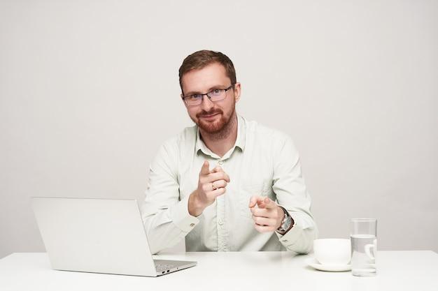 白い背景のテーブルに座って、カメラで上げられた人差し指で見せながら前向きに笑っているアイウェアのうれしい若いかなりひげを生やした男性