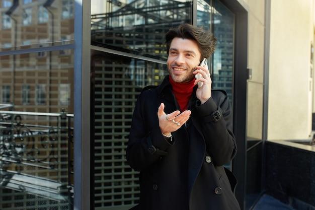 晴れた日に屋外でポーズをとって、電話で会話し、幸せそうに笑っている間、感情的に手のひらを上げるトレンディなヘアカットを持つうれしい若いかなり茶色の髪の男