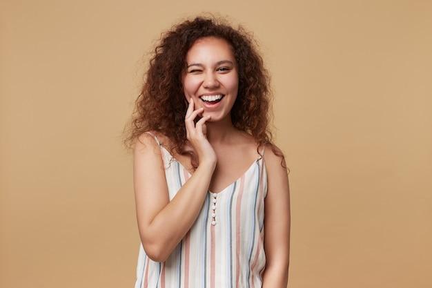 기쁜 젊은 꽤 긴 머리 곱슬 여자 제기 손으로 그녀의 뺨을 만지고 줄무늬 상단에 베이지 색에 서있는 동안 쾌활하게 윙크