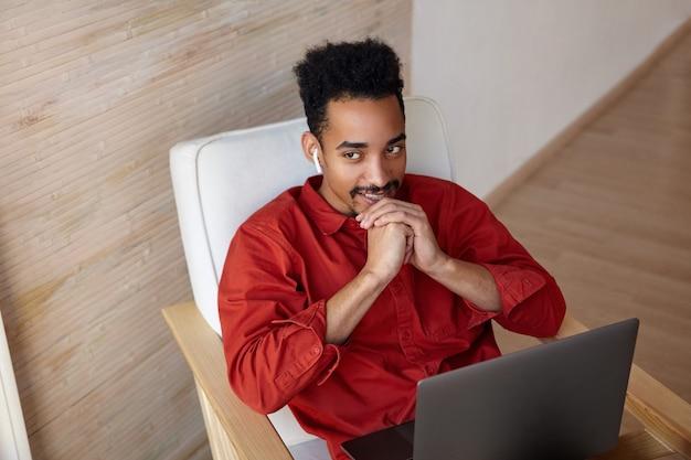 Felice giovane dai capelli corti barbuto maschio dalla pelle scura con il computer portatile sulle ginocchia piegando la mano alzata sul mento e sorridendo positivamente mentre è seduto sulla sedia sull'interno della casa