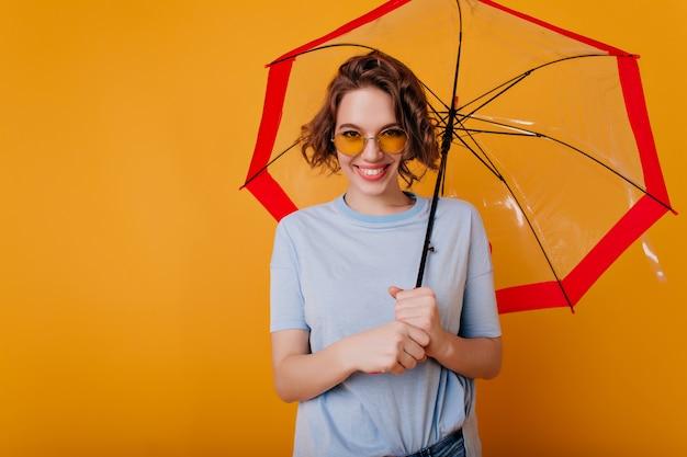 Felice giovane donna in maglietta blu che tiene ombrellone alla moda. ritratto dell'interno della ragazza riccia soddisfatta in occhiali da sole in posa con il sorriso sotto l'ombrello.