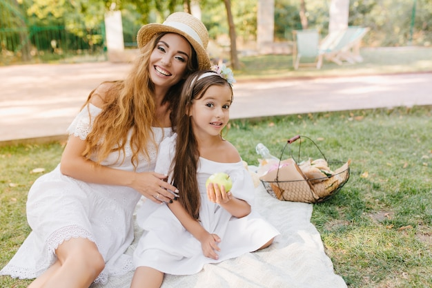 Glad young woman in elegant attire gently embracing girl, eating green apple with appetite. outdoor portrait of happy family having lunch in park and joking.