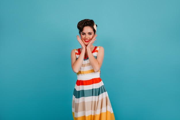 顔に触れる明るいドレスでうれしい若い女性。エレガントな髪型の魅力的なピンナップガールのスタジオショット。