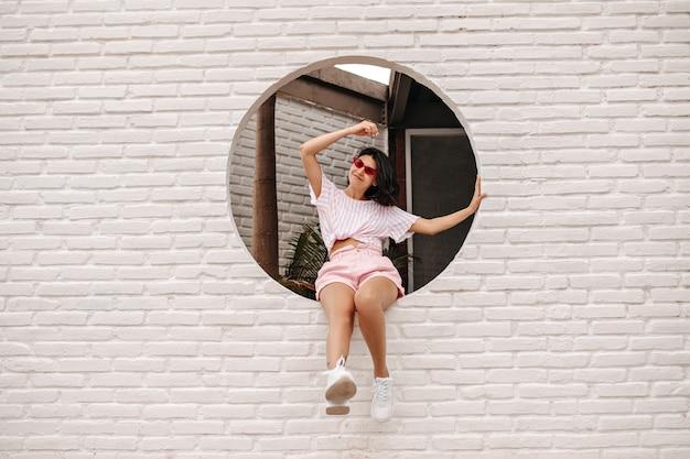 벽돌로 벽에 앉아 좋은 분위기에서 다행 젊은 여자. 미소로 도시 배경에 포즈 행복 갈색 머리 여자의 야외 샷.