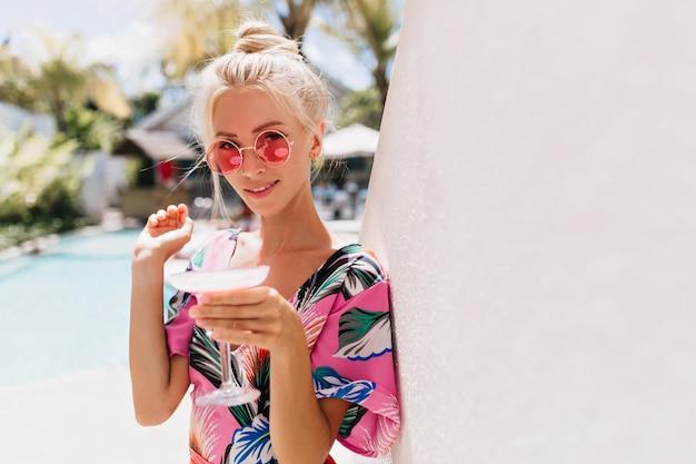 Радостная молодая женщина в модном платье отдыхает на курорте.