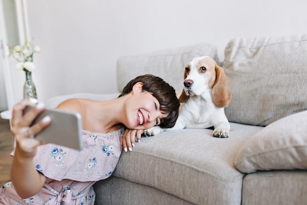 ソファの横に座って子犬と一緒に自分撮りを作る流行のドレスを着たうれしい若い女性
