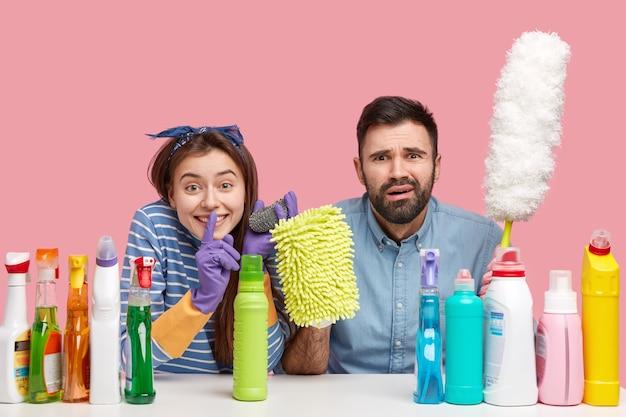 嬉しい若い女性は沈黙のジェスチャーをし、噂を広めないように頼み、欲求不満のひげを生やした夫の近くに座って、洗剤に囲まれています