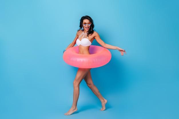 Рад, что молодая женщина позирует с плавательным кругом