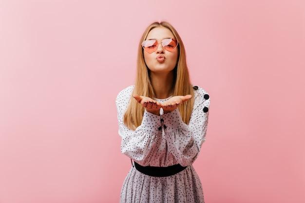 Felice giovane donna che manda un bacio d'aria durante il servizio di ritratti. affascinante donna caucasica in camicetta casual che esprime amore.