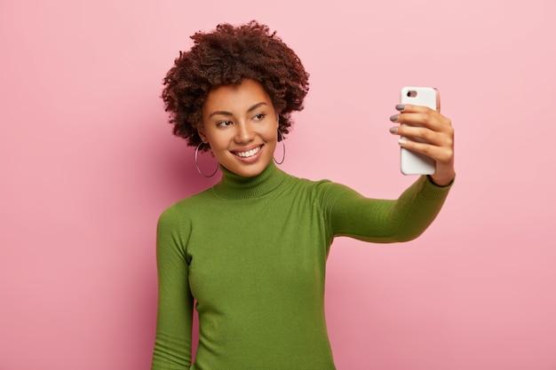 嬉しい若い女性はスマートフォンで自分の写真を撮り、心地よい笑顔で、緑のタートルネックのジャンパーを着て、アフロの髪型をしていて、ピンクの壁をモデルにしています。自撮りの時間です。