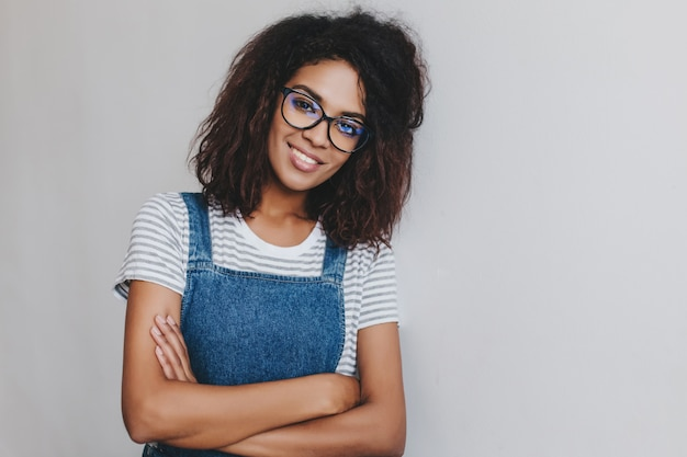 嬉しい若い女性は優しい笑顔でポーズをとってデニムの服と流行のメガネを着ています