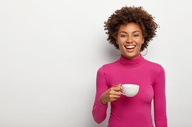 Felice giovane donna indossa poloneck rosa, tiene la tazza con caffè, gode del tempo libero per la comunicazione dal vivo con l'amico
