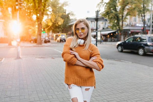 Felice giovane donna in pantaloni strappati bianchi in posa per strada con le braccia incrociate