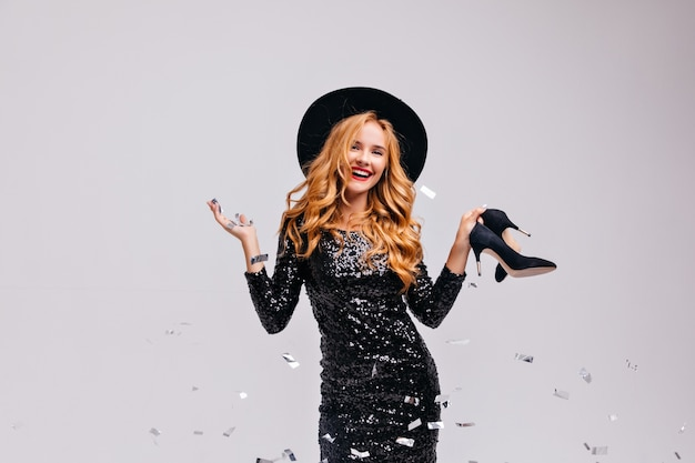 Glad young woman with blonde hair holding her shoes and smiling.  portrait of elegant european female model in hat isolated on white wall.
