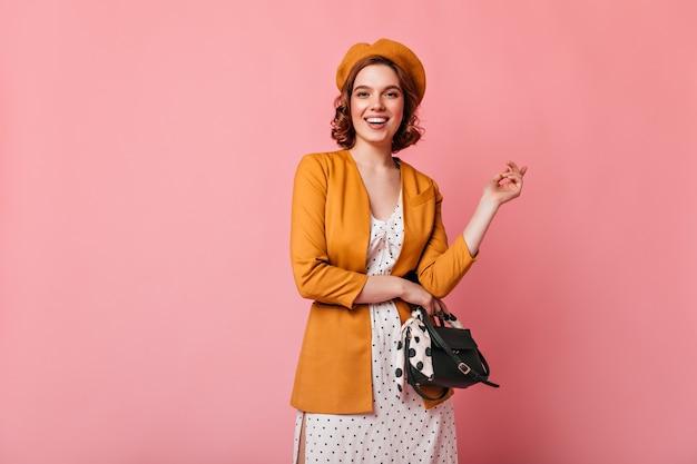 カメラを見てハンドバッグでうれしい若い女性。ピンクの背景に分離されたベレー帽の素晴らしいフランスの女の子のスタジオショット。
