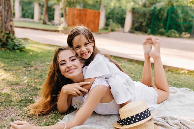 Рад, что молодая женщина с блеском макияжа охлаждает на одеяле с ногами и улыбается. смеющаяся загорелая девушка, лежащая на спине матери
